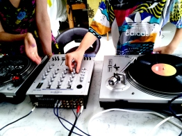 He is shown the basix tools required to play his music using the turntables and dj mixer.